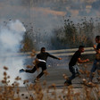 Men run away from cloud of tear gas smoke