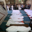 People pray at the mosque over 17 bodies wrapped in shrouds