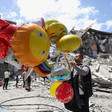 A man holds large, colorful balloons against a backdrop of ruins