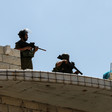 Two armed officers stand on the roof of a brick building