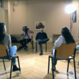 A group of people sitting in a circle are filmed