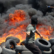 A man wields a slingshot in front of burning tires