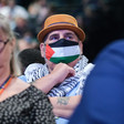 Man in hat wears Palestinian headscarf and facemask in colors of Palestinian flag
