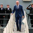 Simon Coveney walks on steps surrounded by three others in naval uniform