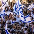 Man in crowd waving Israeli flags