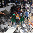Rescue workers surrounded by rubble carry a stretcher