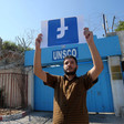 A man holds the Facebook logo upside down in front of the UNSCO building