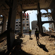 Two men stand on sand inside concrete skeleton of badly damaged building