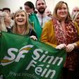 Smiling people hold Sinn Fein banner