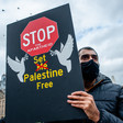 Man wearing face mask holds placard calling for freedom for Palestinians