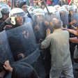 Protesters push at shields held by police wielding batons.
