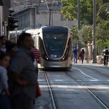 Passengers wait as light rail train approaches