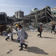 Children walk past rubble of destroyed buildings