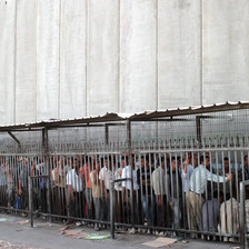 Palestinian men queue at checkpoint next to very tall concrete wall