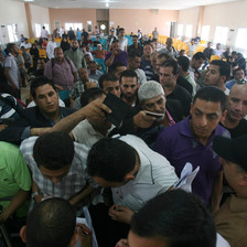 Men holding passports crowd at crossing terminal