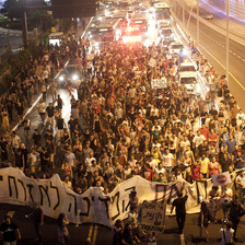 Protesters march down a highway carrying banners and signs