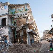 Boy walks past destroyed building exposing mural of Dome of the Rock in Jerusalem