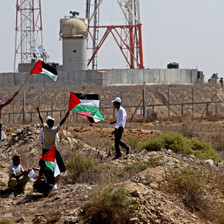 Youths holding Palestinian flags stand in front of Israel's border wall and military jeep