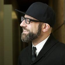 Portrait photograph of bearded man wearing cap