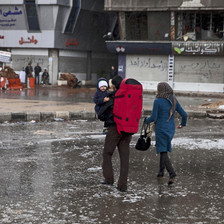 Couple carrying baby cross flooded street in war-torn camp
