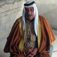 Candid portrait of older man wearing long robes and traditional headdress