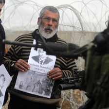 Middle-aged man holds photo of Mandela in front of heavily armed Israeli soldier