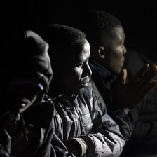 Close-up of men wearing winter coats sitting at night