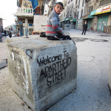 Boy sits on cement block which is spray painted with a stencil reading Welcome to apartheid street