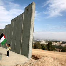 Girl holding Palestine flag stands next to section of 25-foot-tall concrete wall under construction