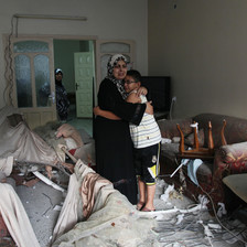 A mother hugs her adolescent son in a bombed-out living room