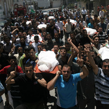 Crowd of men carry shrouded bodies during funeral procession
