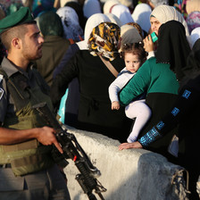 Israeli soldier carrying gun stands in front of queue of women and children at checkpoint