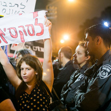 A pair of Israeli police officers, one a woman and the other a man, watch as a protesting woman holds a Hebrew-language sign over her head