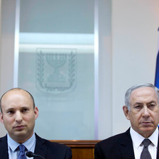 Naftali Bennett and Benjamin Netanyahu stand shoulder-to-shoulder in front of Israeli flag