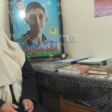 Woman with covered face sits next to table and poster of her smiling teenage son