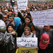 Men and women hold Arabic-language signs protesting salary cuts during large demonstration