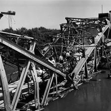 Black and white photo shows people walking across badly damaged bridge