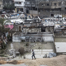Wide view of boy walking in front of flooded neighborhood of shanty dwellings