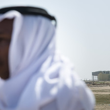 Man wearing head wrap stands in open land in front of power plant