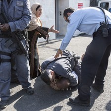Elderly woman gestures her arm towards police officer as he stands over another officer who has pinned man to the ground