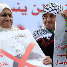 Elderly women hold up posters protesting the Balfour declaration