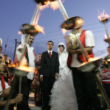 A bride and groom walk through a procession of men in traditional dress carrying burning torches