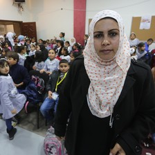 A young woman looking at the camera stands in front of a crowded hall of schoolchildren