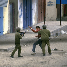 A young Palestinian man gestures towards an Israeli soldier cocking his rifle while being grabbed at by another soldier on the street