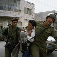 Photo shows an Israeli soldier with his arm around the neck of a Palestinian youth as other soldiers look on