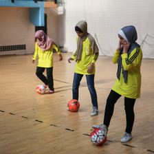 Three girls manipulate footballs with their feet in a gymnasium
