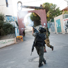Photo shows soldiers firing tear gas in front of gate to Aida camp that has a giant key on top of it