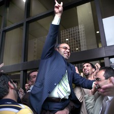 Man in middle of crowd smiles while making victory hand gesture outside court building