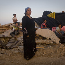 A woman wearing a long black dress stands in foreground as children sit on the rubble of a razed structure in the background