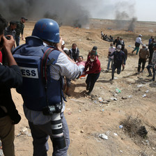 Photographer wearing flak jacket marked as PRESS and wearing a blue helmet is seen from behind while taking photos of demonstrators